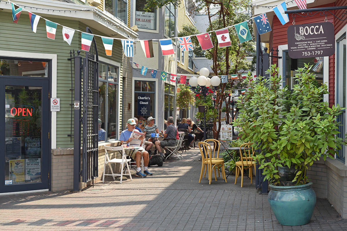 People enjoy the outdoor tables underneath colourful signs and awnings in Nanaimo's historic Old City Quarter district. Don Denton photography